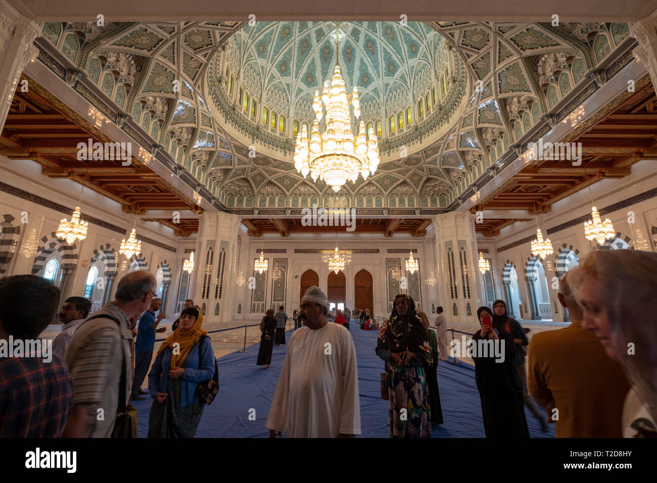 Tourists inside the prayer hall at Sultan Qaboos Grand Mosque in Muscat, Oman - Stock Image