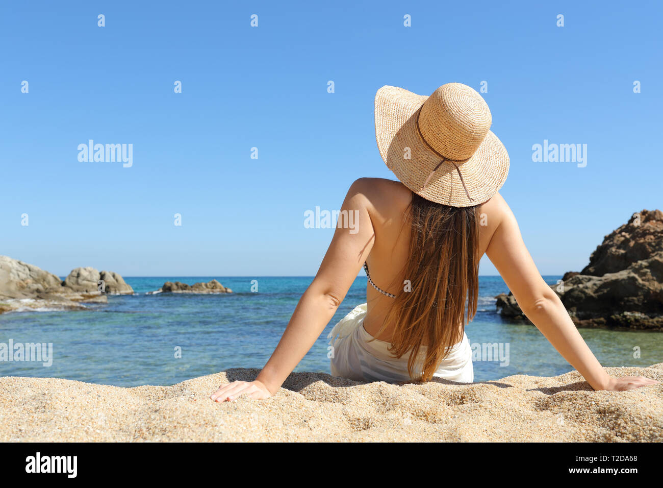 Back view portrait of a sunbather relaxing sitting on the sand of the beach on summer vacation - Stock Image