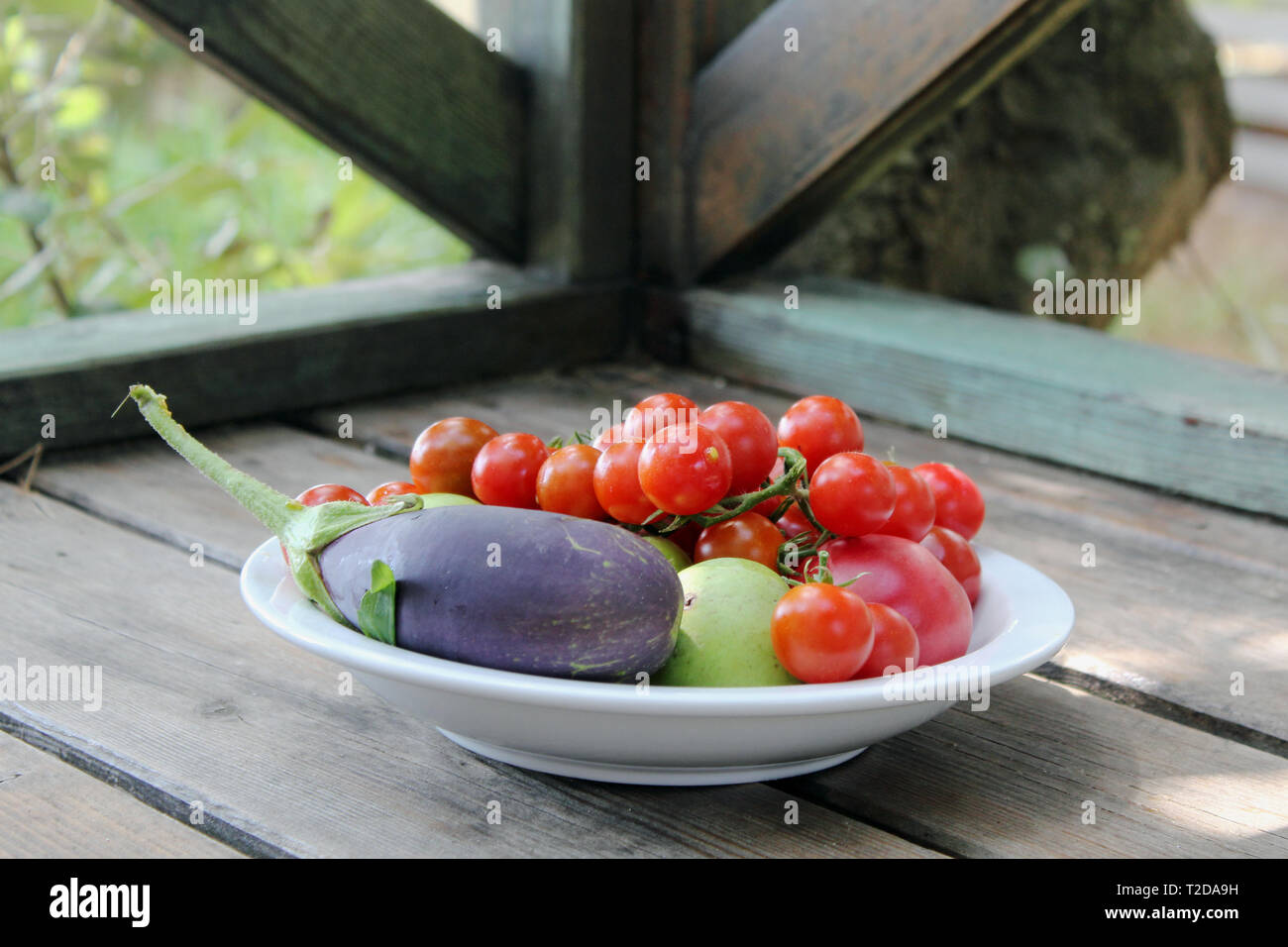 A plate with fresh vegetables and fruits - Stock Image