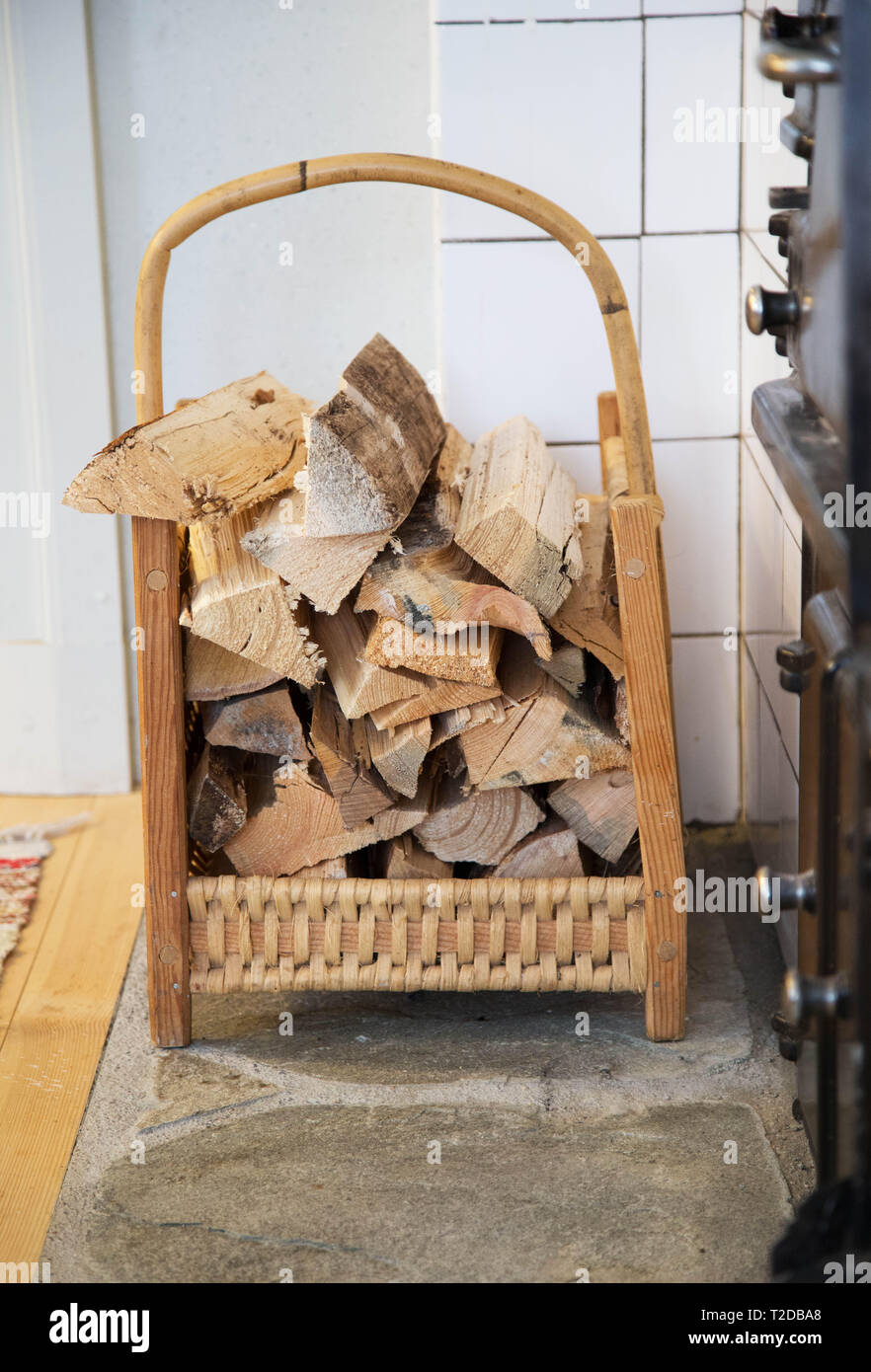 Firewood at a wood stove in kitchen. - Stock Image