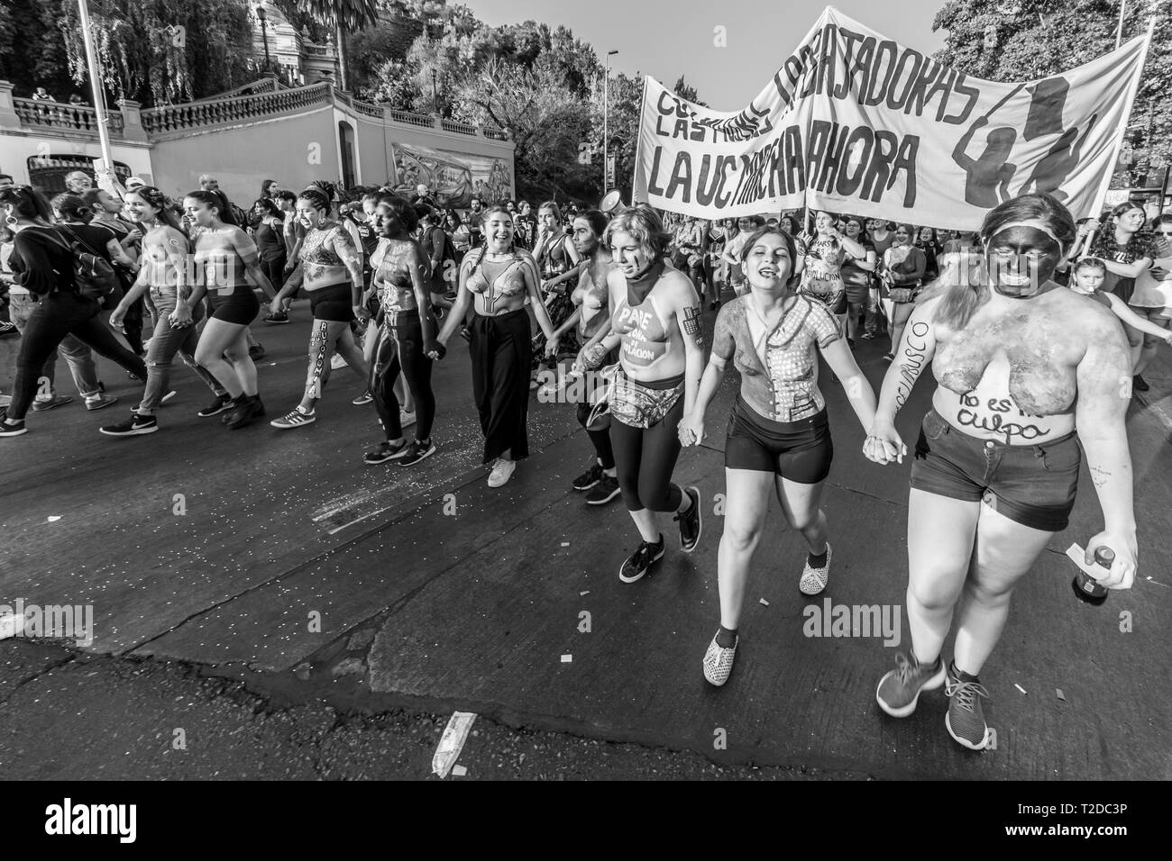 A view of Santiago city center streets during the women's day demonstration. People carrying protester signs during Women`s Day 8M - Stock Image