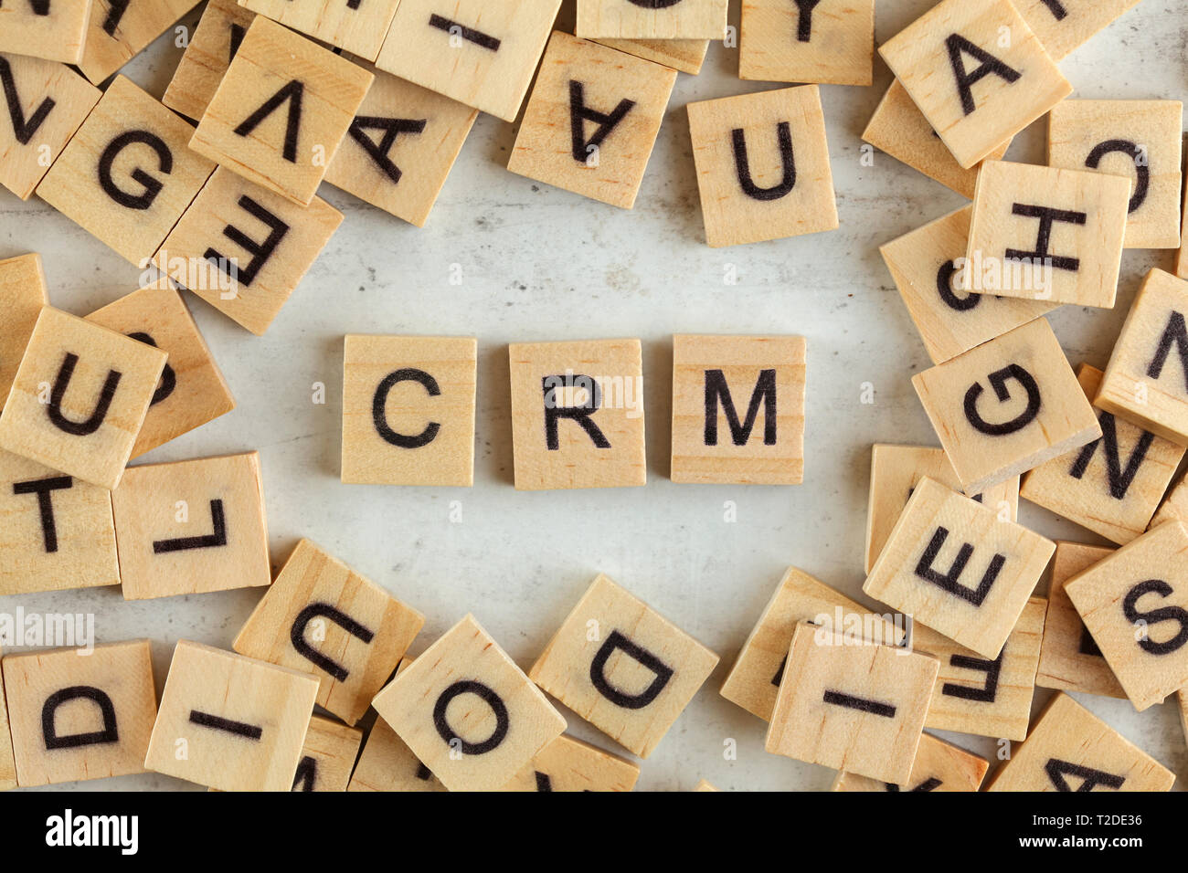 Top down view, pile of square wooden blocks with letters CRM stands for Customer Relationship Management on white board - Stock Image