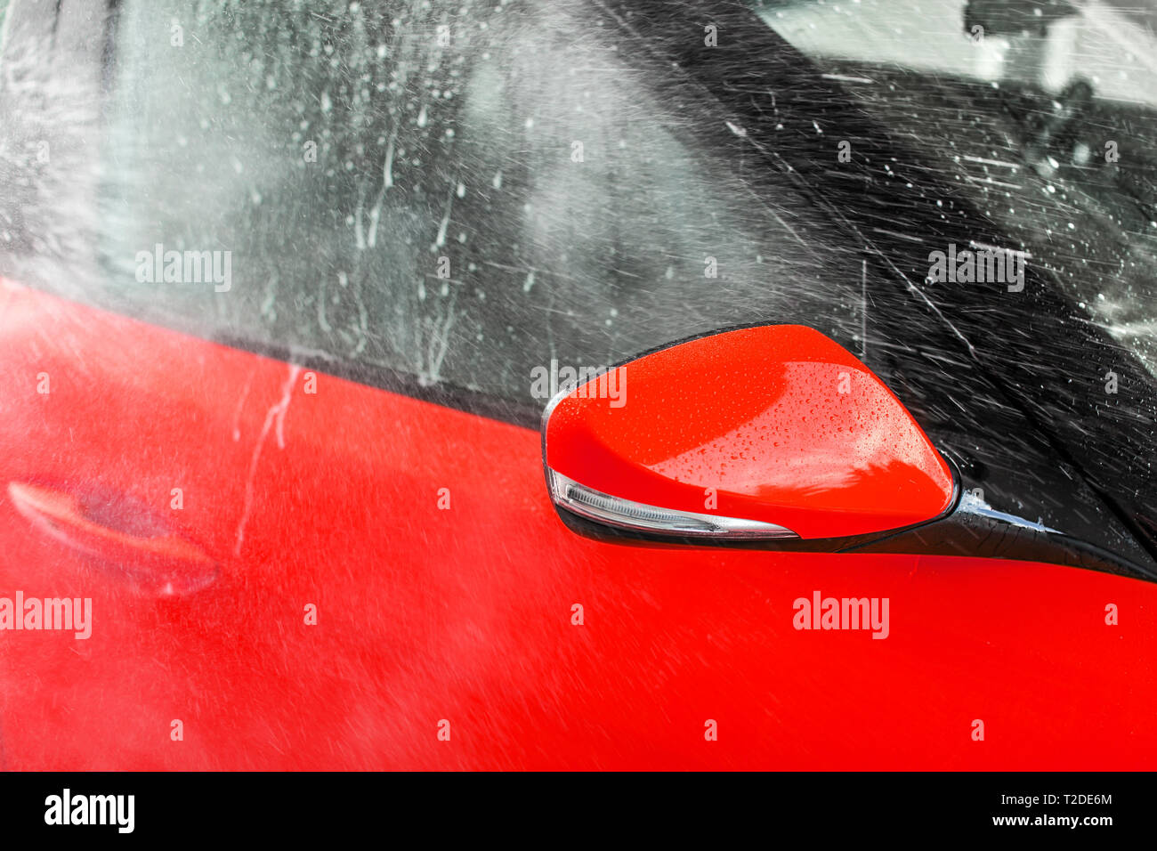 Side mirror of bright red car washed in self serve carwash, water spraying on the glass. Stock Photo