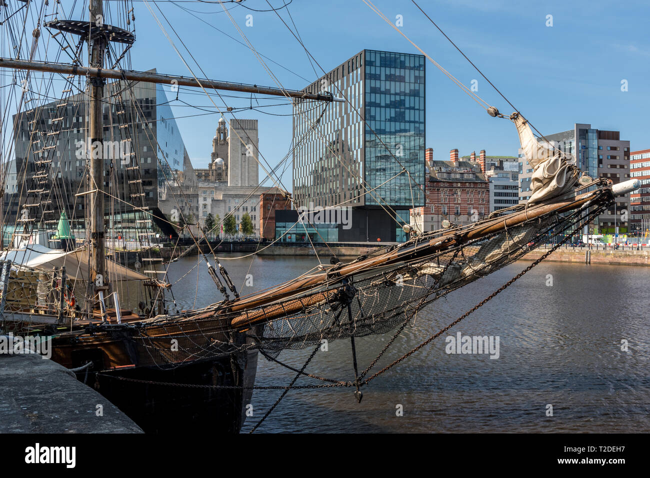 Old square rigged sailing ship moored in front of modern glass office buildings - Stock Image