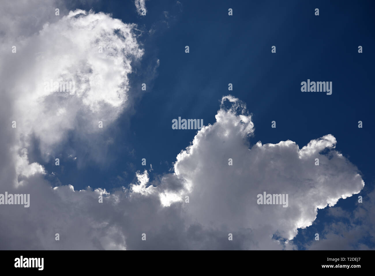 Rays of sunshine reflecting off fluffy white clouds and deep blue sky. - Stock Image