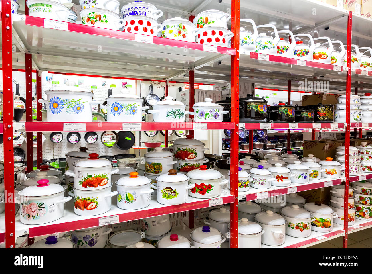 Samara, Russia - March 30, 2019: Different bright metal enamelware, cooking pots containers utensils for sale on store shelf - Stock Image