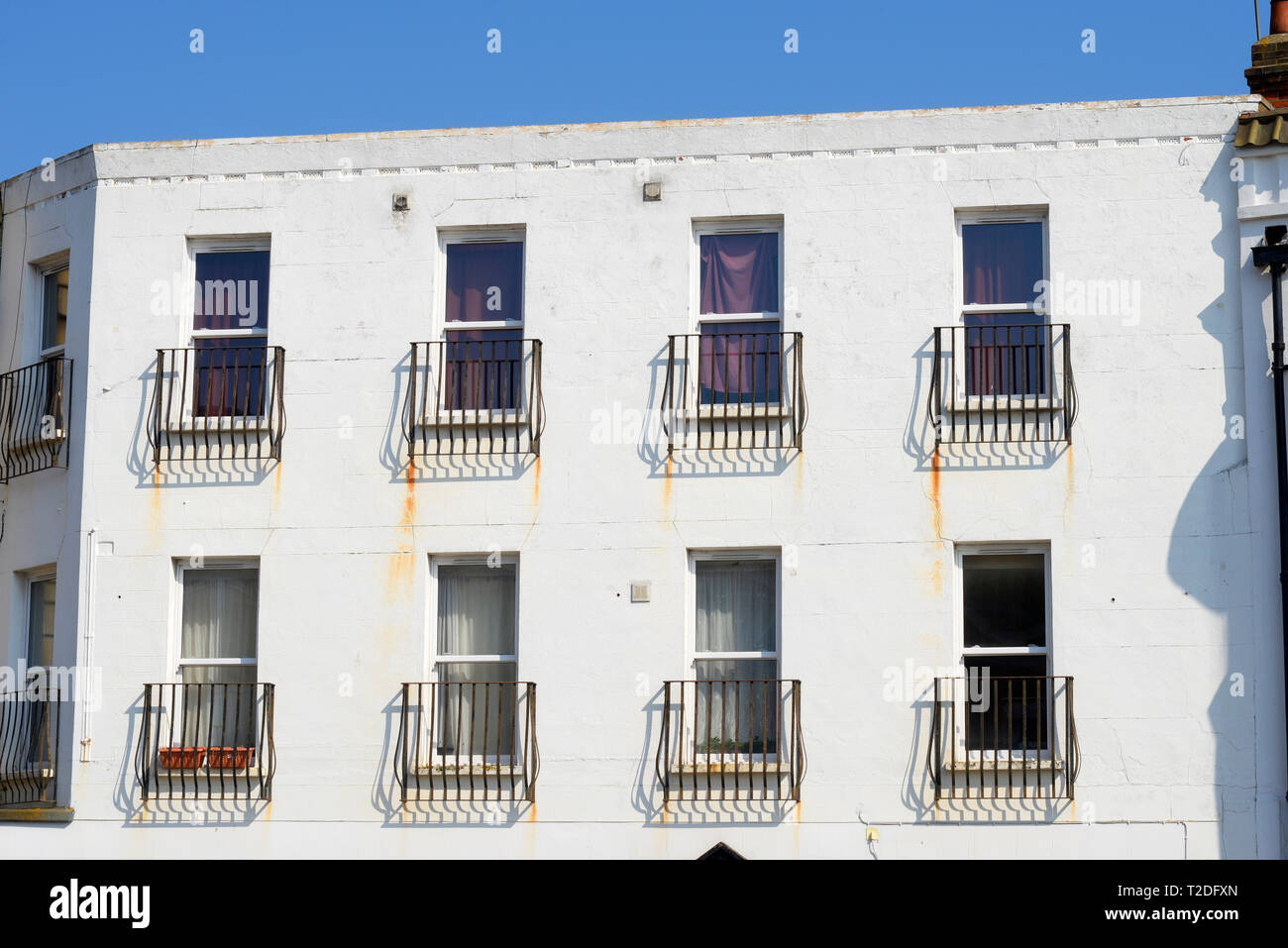 Plain bright white building with rust stains from metal Juliet balconies. Spoiled white paint. Balconet, balconette railings on facade. Space for copy - Stock Image