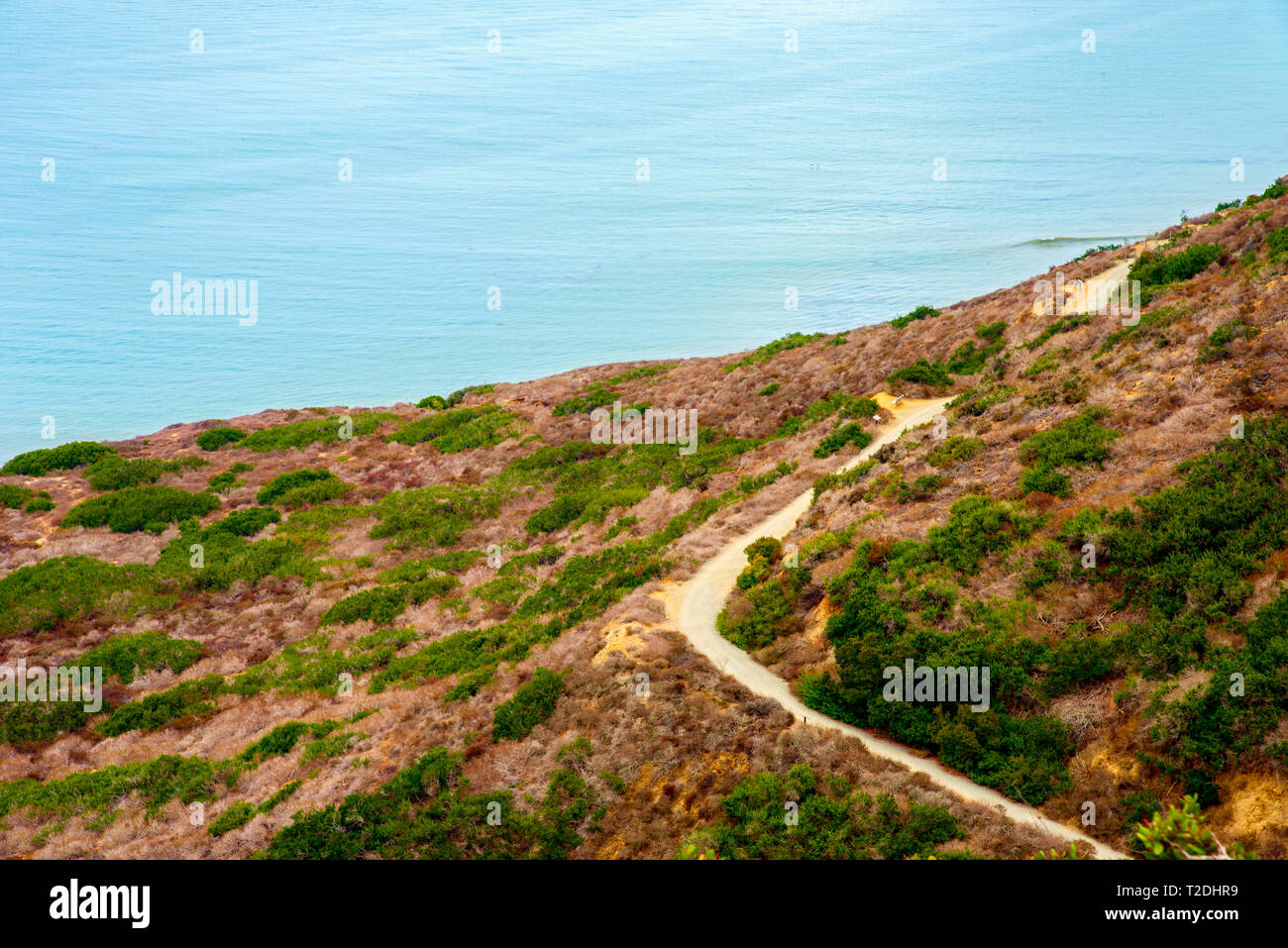 Looking down onto mountain road with blue ocean below. Road curving around mountainside. - Stock Image
