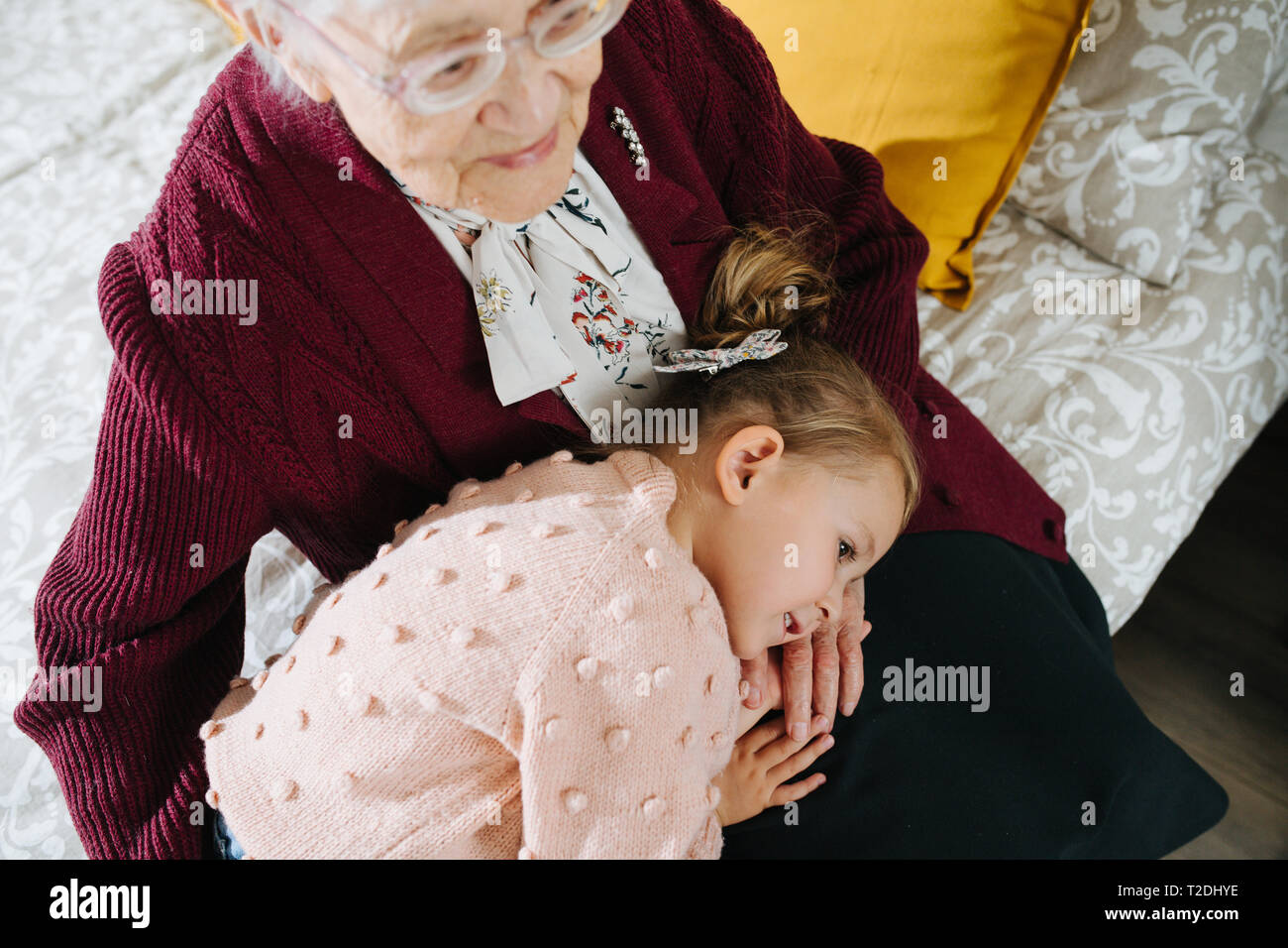 Happy moments with great grandma, senior lady spending quality time with her great granddaughter. Restless naughty little girl taking a nap on her gre Stock Photo