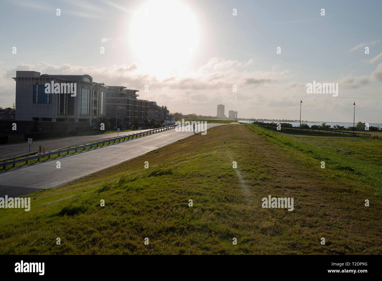 A bicyclist hitting the Lakefront Trail, along Lake Pontchartrain, in the Bucktown neighborhood of New Orleans, Louisiana. - Stock Image