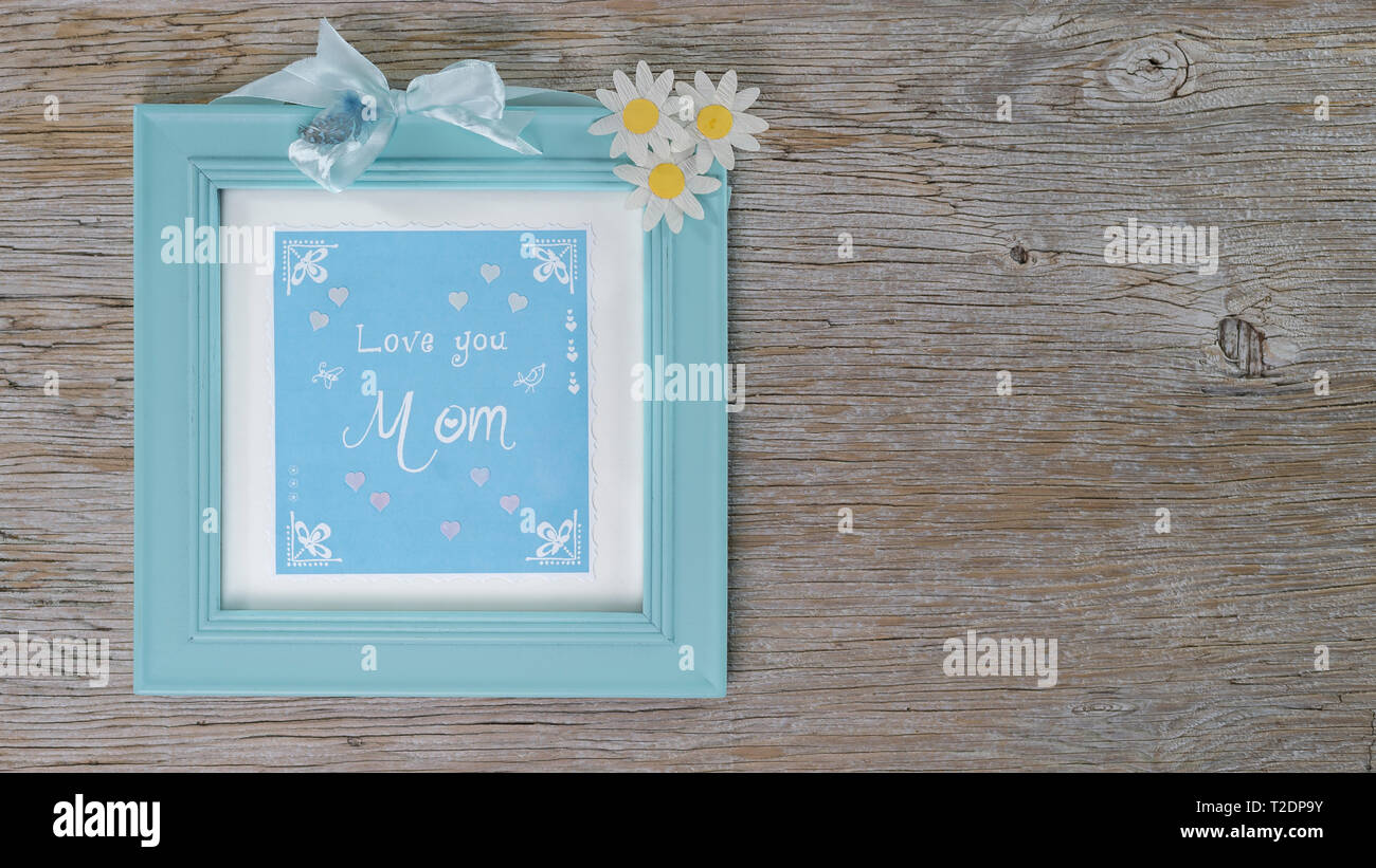 Mint colored wooden frame with hand lettering text in english: Love you mom. Wood background with copy space. Flowers of the Magerite. - Stock Image