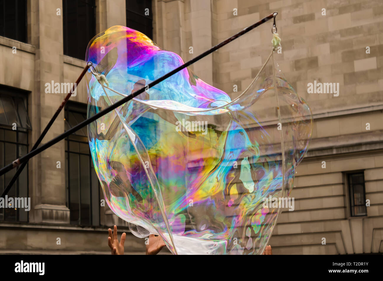Multi-ethnic group of little friends with toothy smiles on their faces enjoying warm sunny day while participating in soap bubbles show. - Stock Image