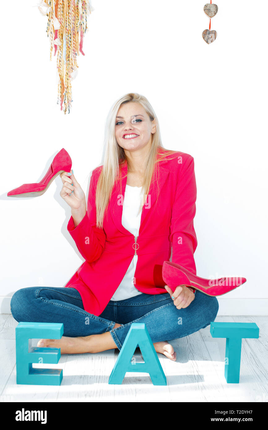 Young stylish slim woman playing with high heels while sitting on floor - Stock Image