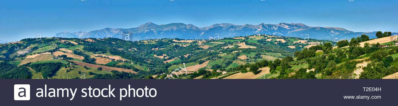 A beautiful panoramic view with blue skies over the hills of Le Marche, Italy, with Monti Sibilini in the background Stock Photo
