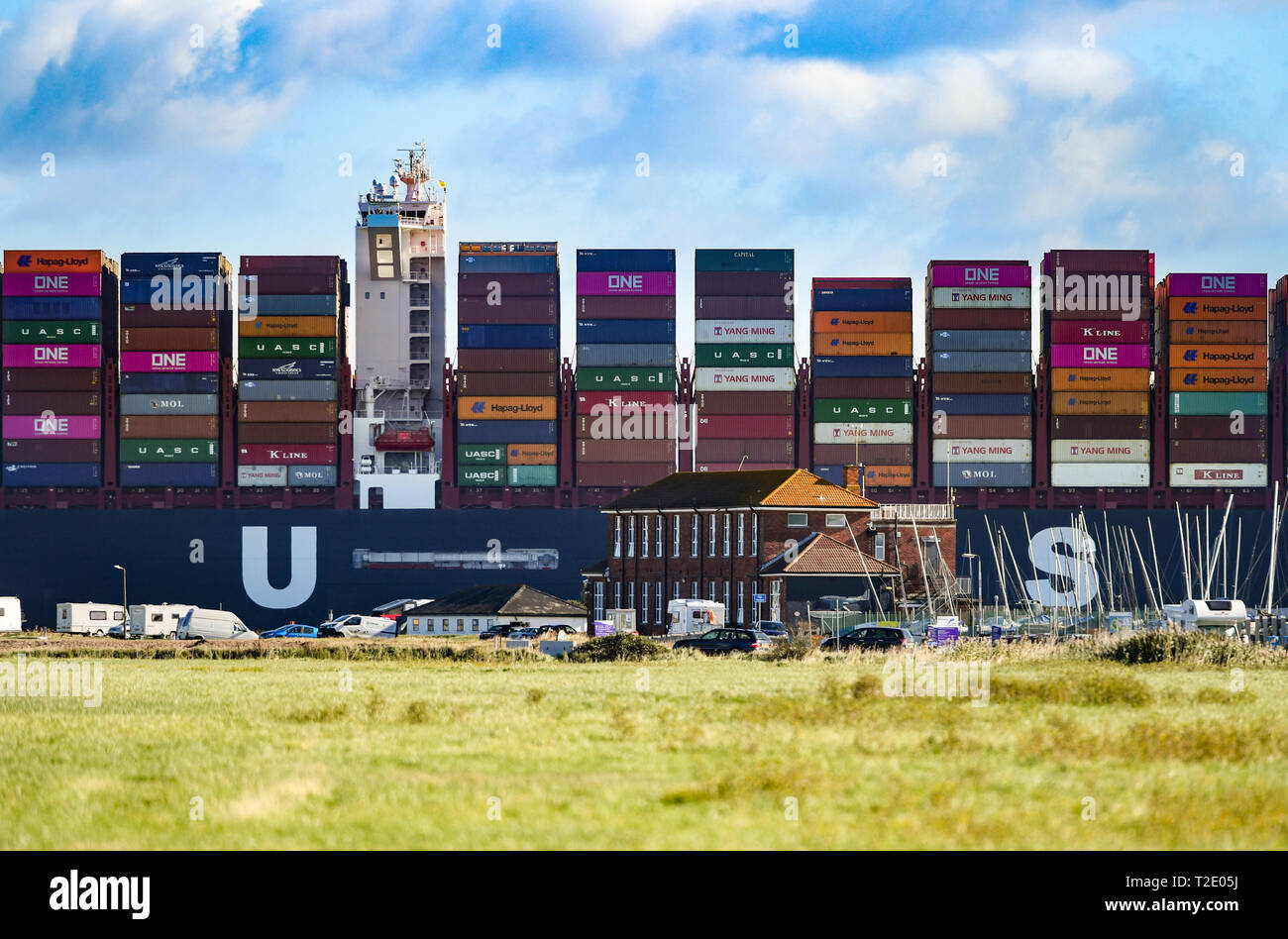 Fully loaded Al Dahna Super Container ship  leaves Southampton Docks dwarfing the buildings of Calshot taking exports across the World. - Stock Image