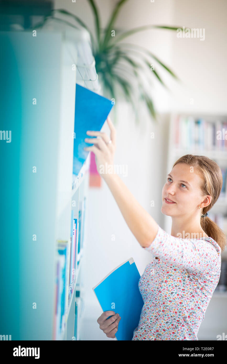 Cute female university/highschool student with books in library - Stock Image