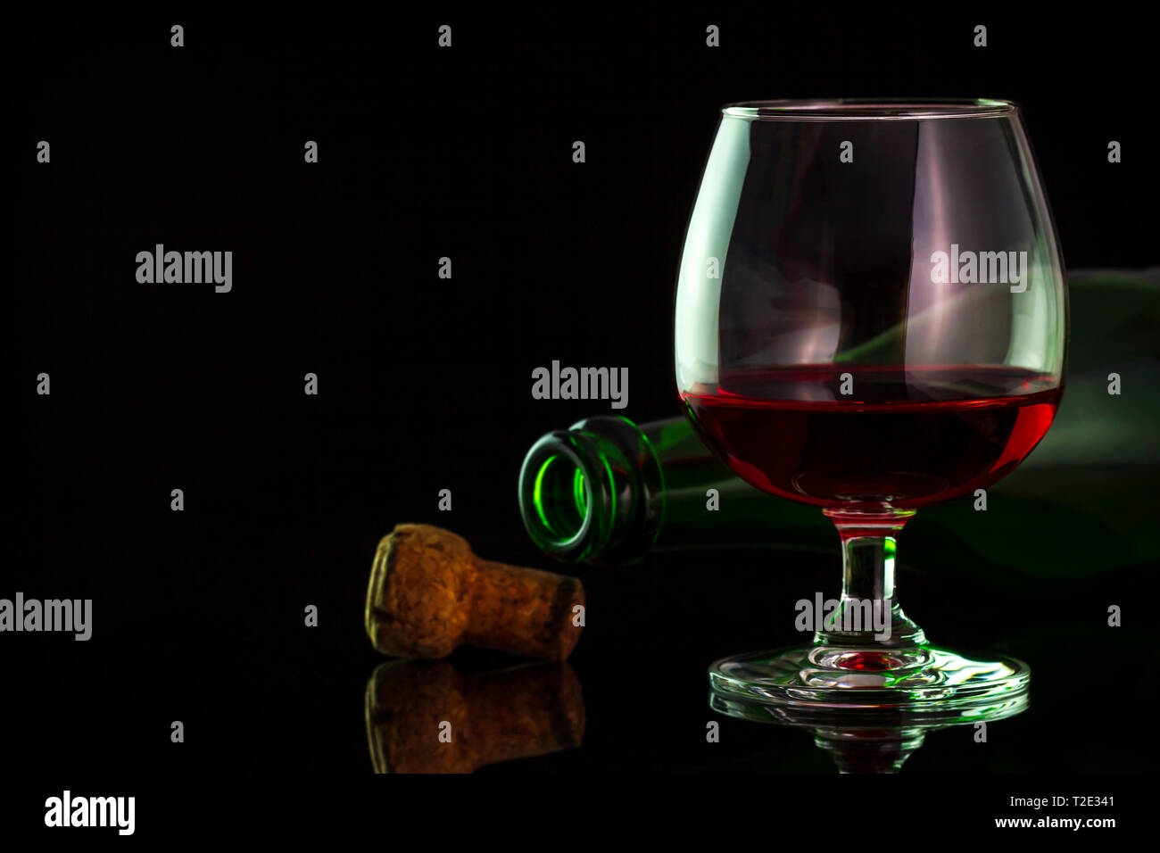 Red wine in glass and bottles on the table in darkness background. Copy space for text or articles. - Stock Image