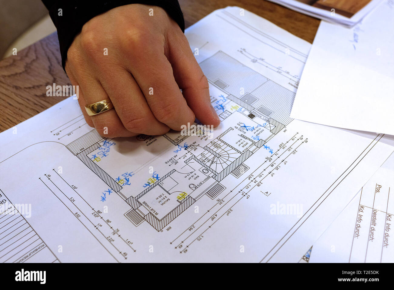 Architect, engineer discussing blueprint of a house with its clients in the office Stock Photo