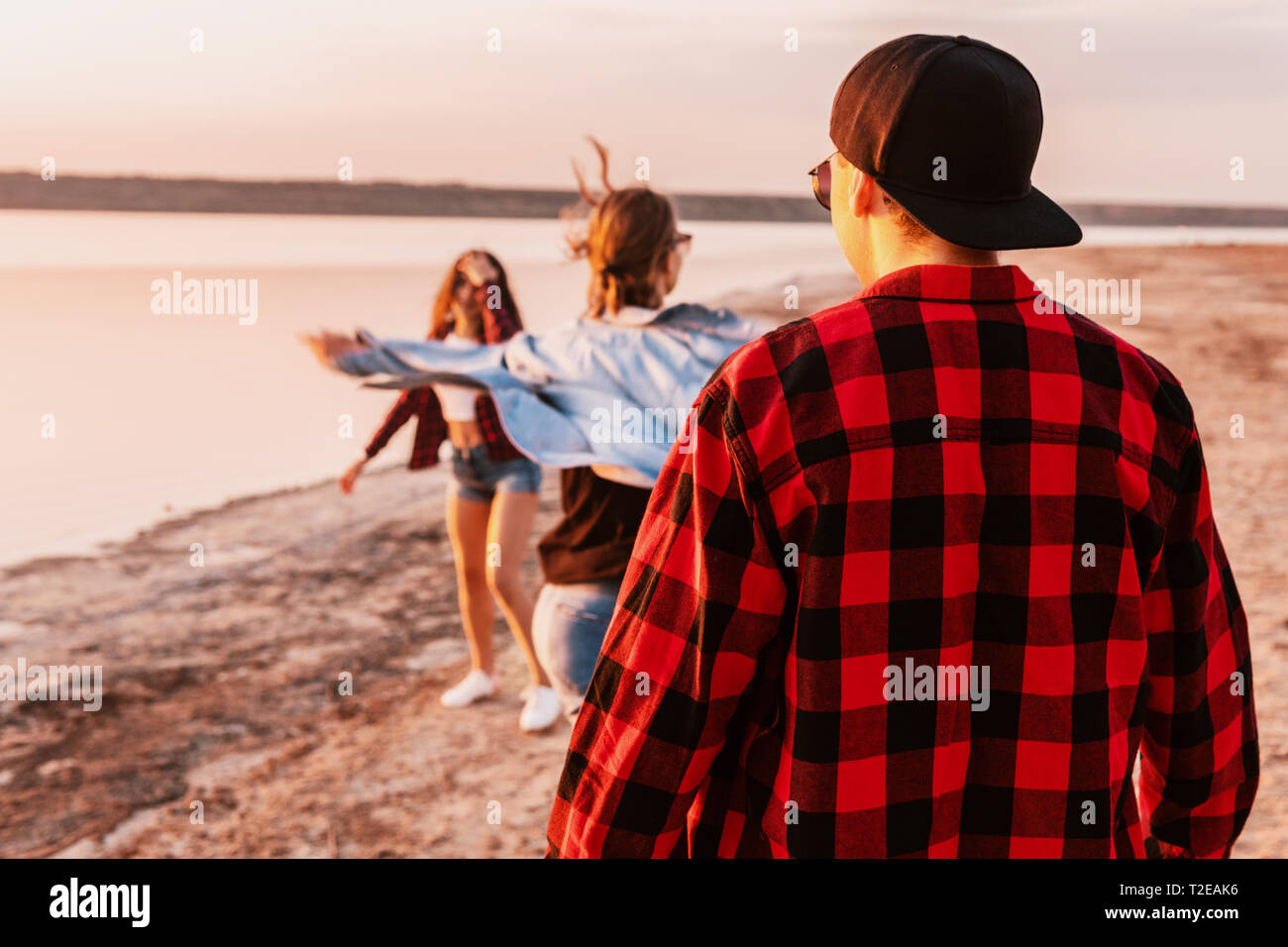 Group of hipster young couples on beach together walking during sunset. Love, relationship and friendship Stock Photo