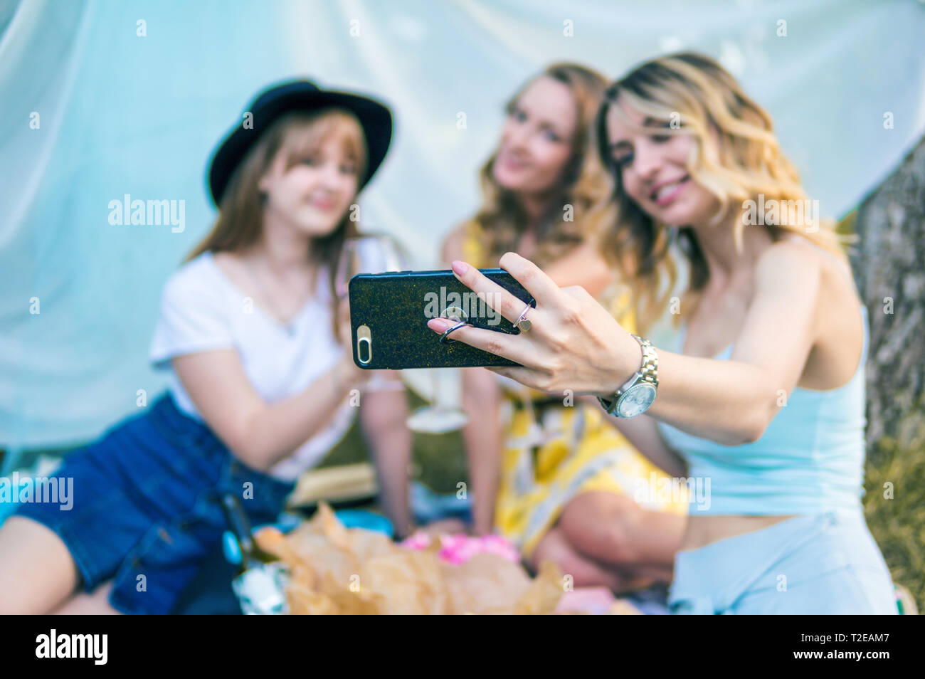 Group of girls friends making picnic outdoor. They make selfie photo from smartphone. bachelorette, party Stock Photo