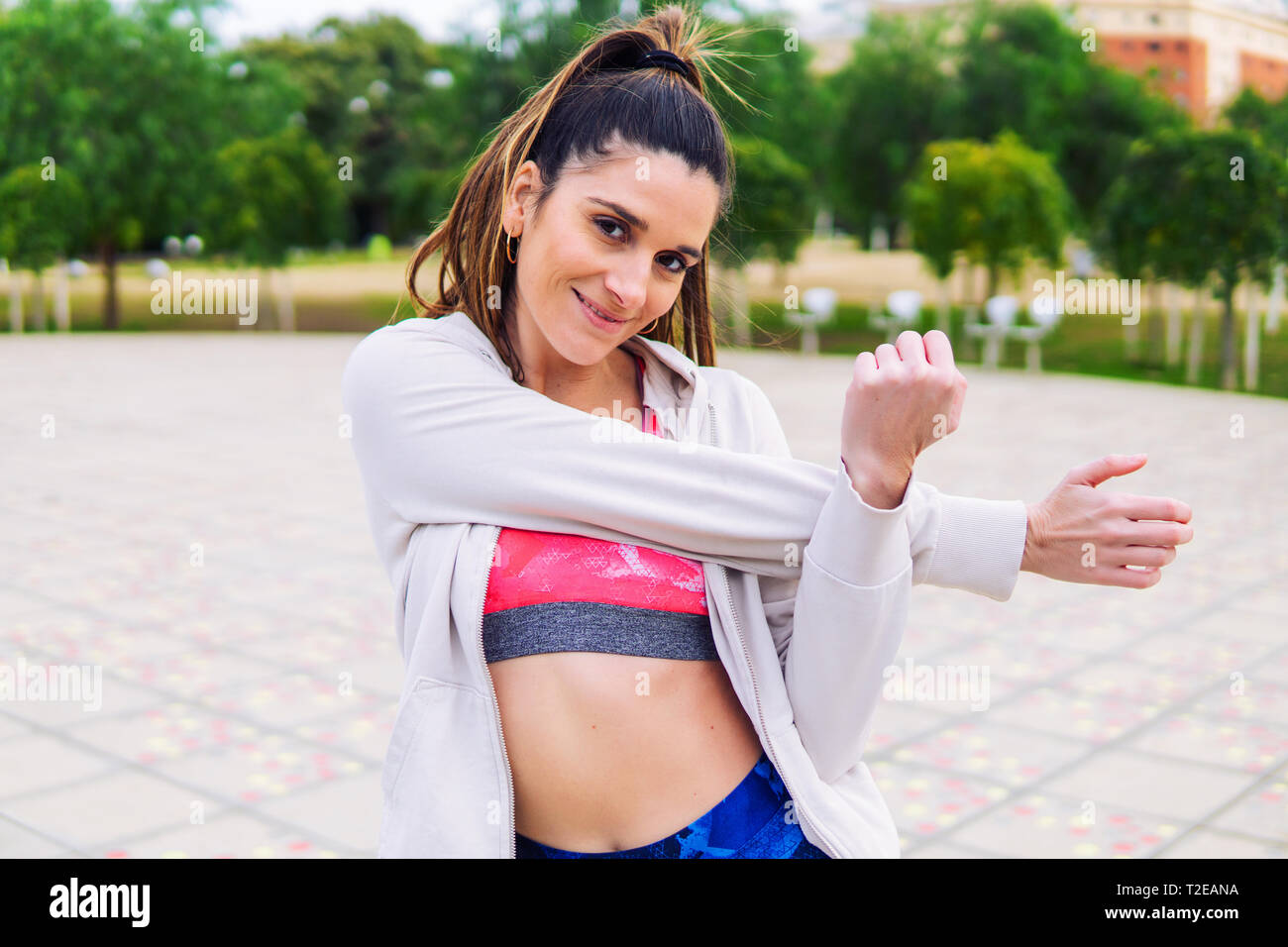 Runner fit woman warming up before sport training in the park. Stock Photo