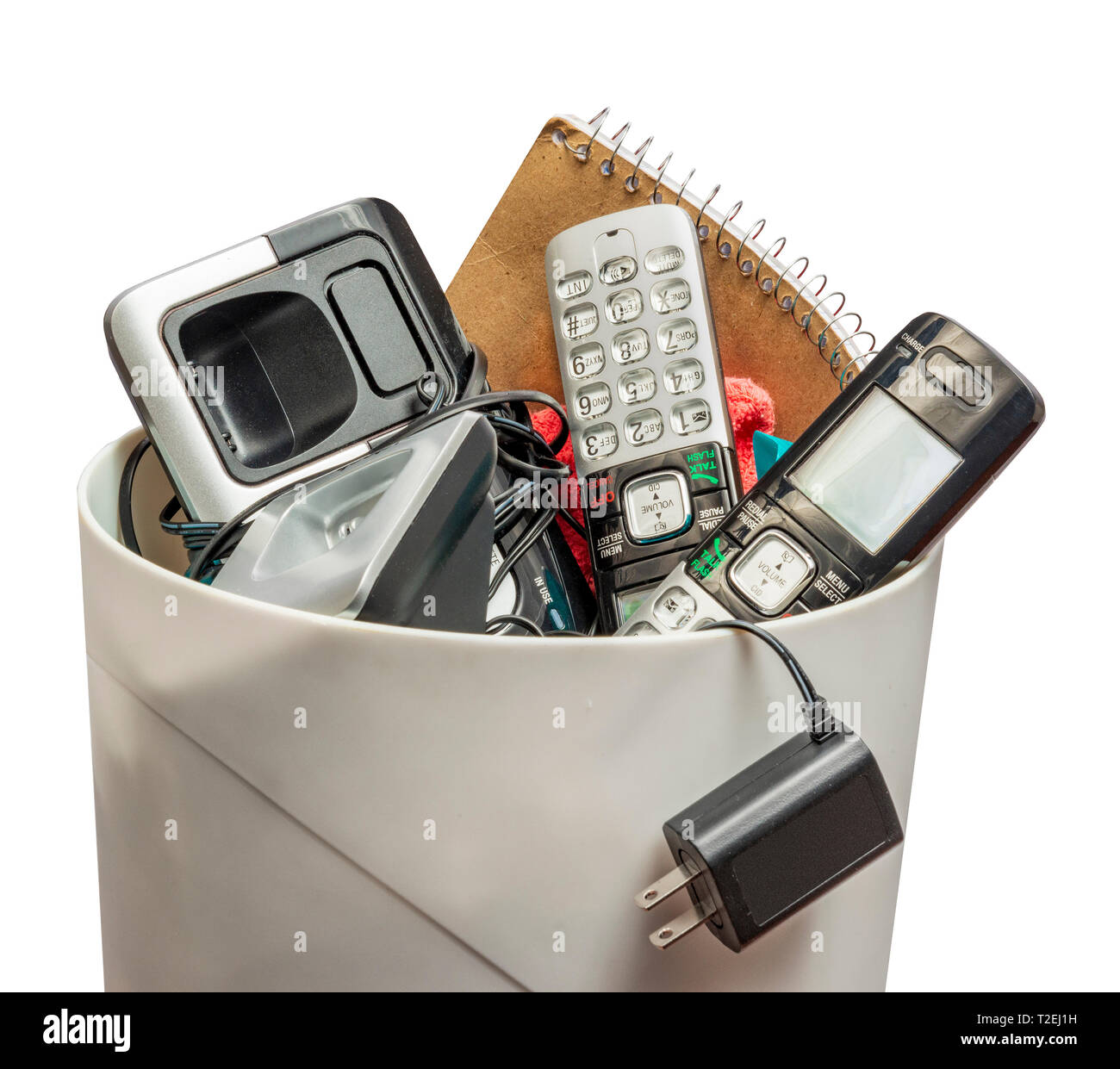 Horizontal shot of land line telephones thrown away in a trashcan.  This shot is from the side.  Only the top half of the trashcan shows. - Stock Image