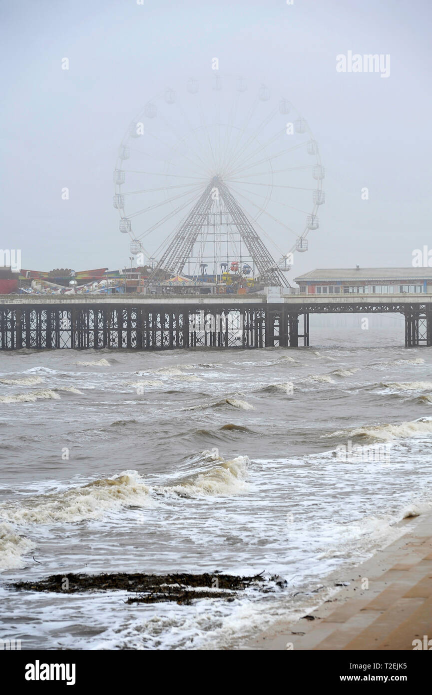 The ferris Wheel on Central Pier in thick fog at high tide,Blackpool,UK - Stock Image