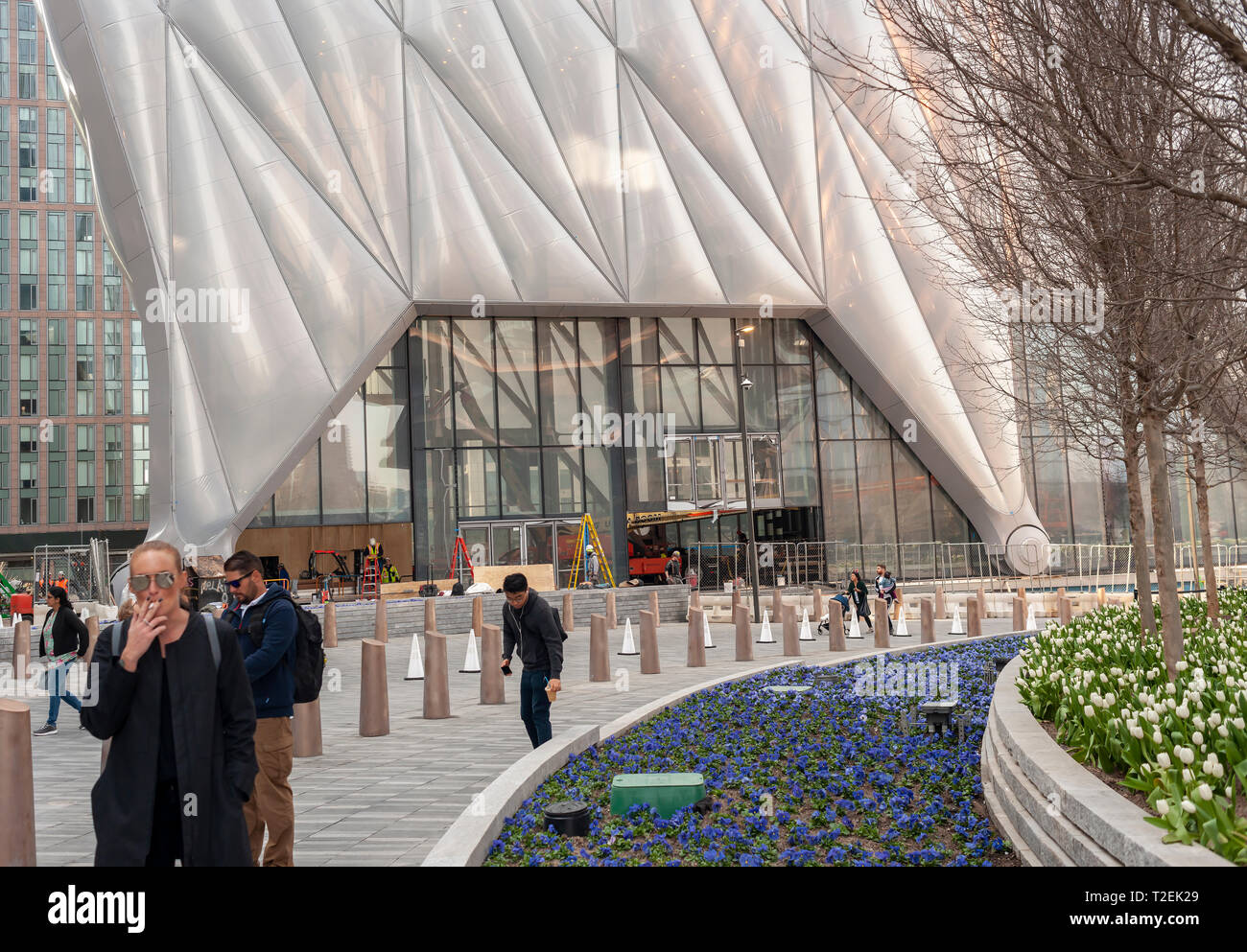 """Tourists in the plaza of Hudson Yards pass """"The Shed"""" arts space as workers prepare it for its opening, seen on Saturday, March 30, 2019 . (© Richard B. Levine) Stock Photo"""