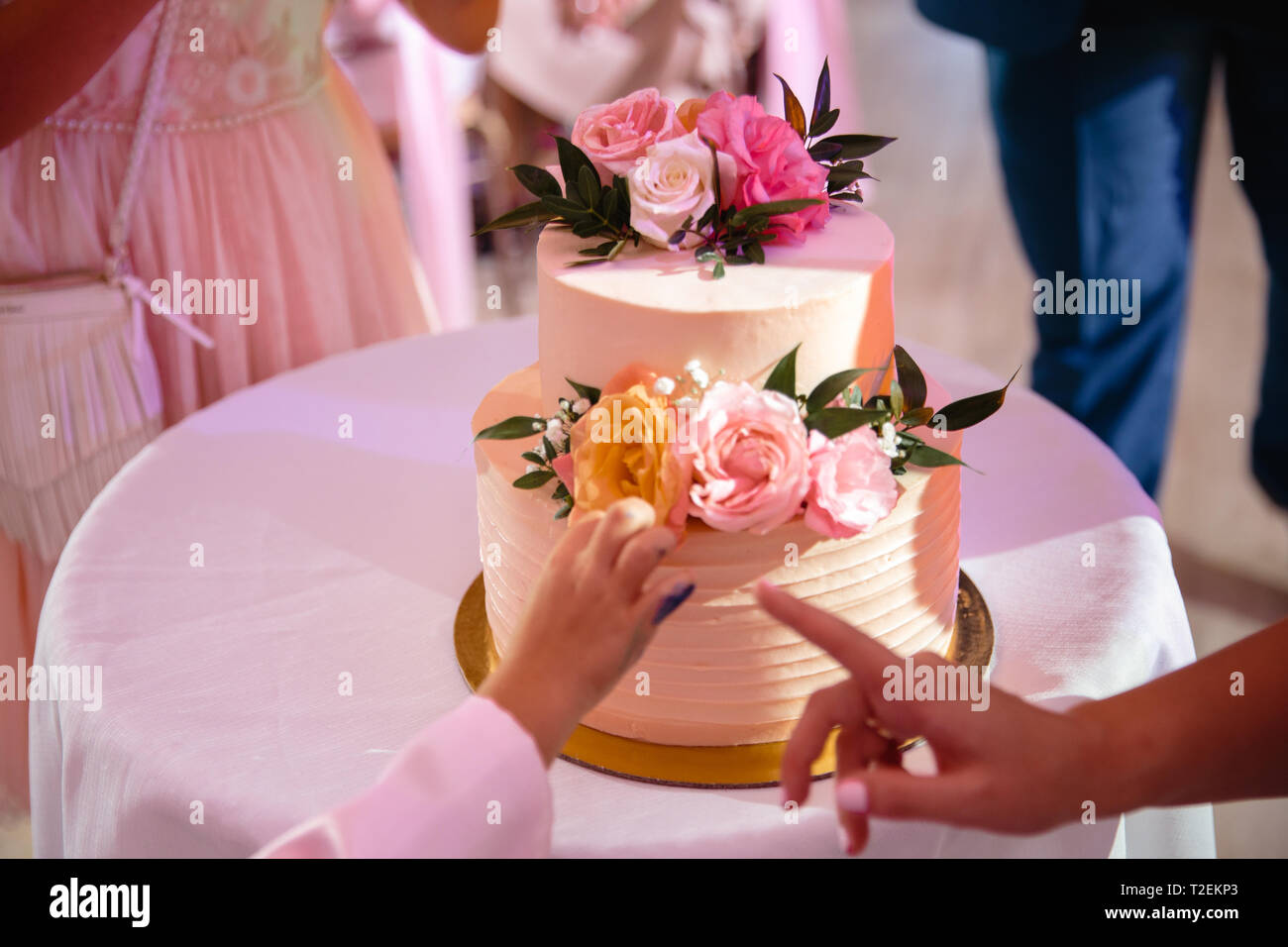 A child's hand leaning toward the wedding cake in ecological natural style - His parent shows with her finger that he shouldn't touch the cake in the  - Stock Image