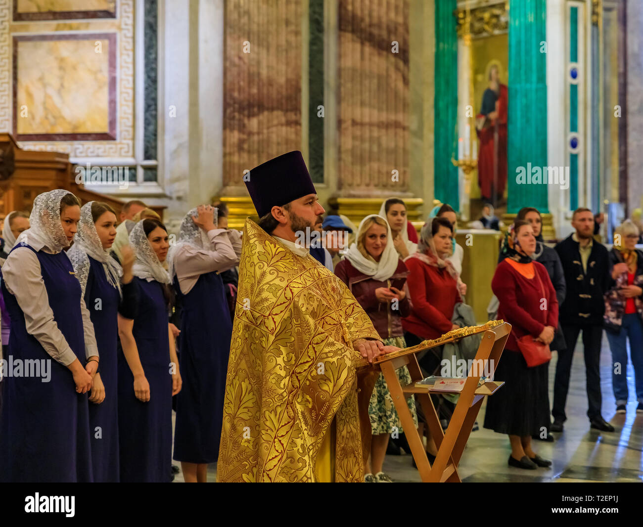 Saint Petersburg, Russia - September 10, 2017: Russian Orthodox priest in traditional clerical clothing serving mass and parishioners behind him in th - Stock Image