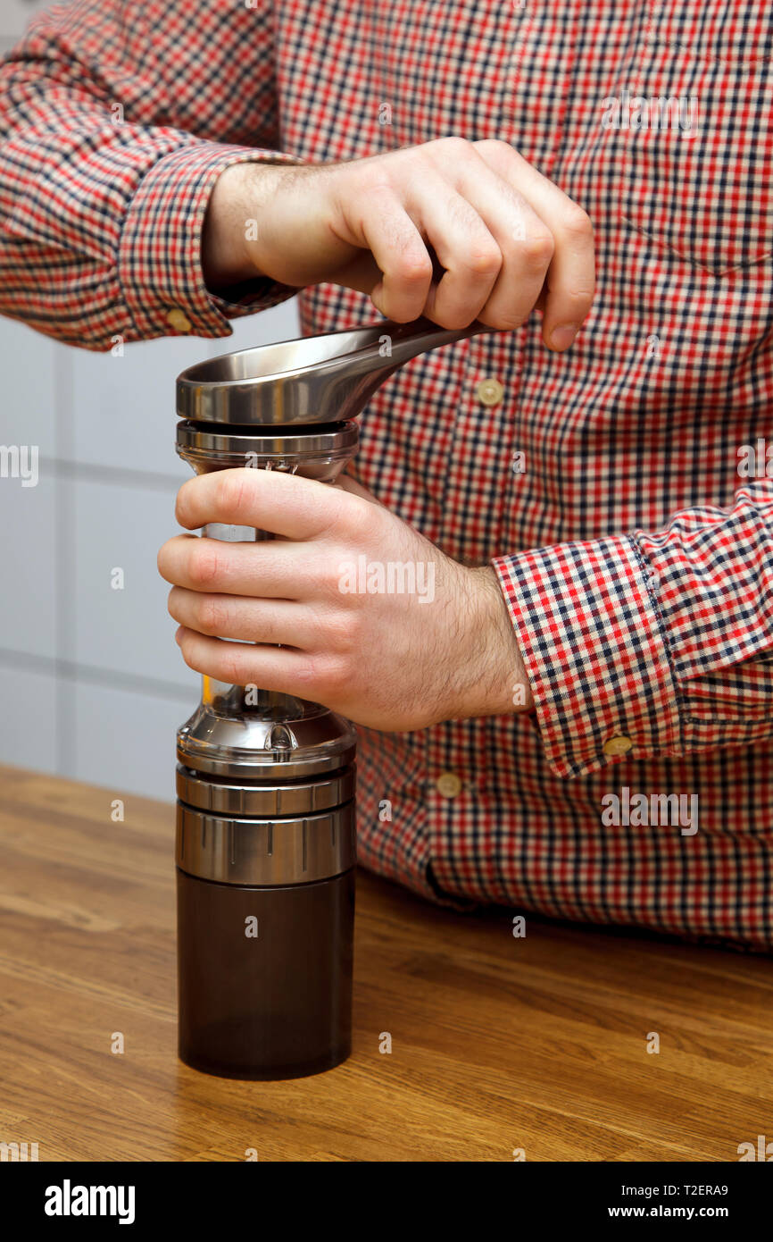 The hands of men make coffee. Barista chops coffee in a coffee grinder. - Stock Image