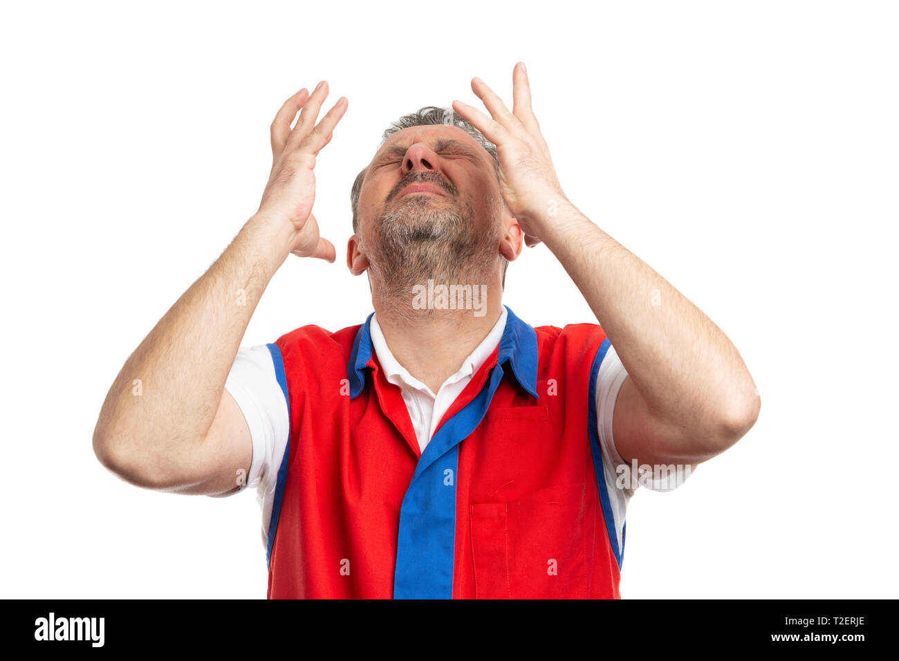 Stressed male hypermarket or supermarket worker with headache making despaired expression and gesture isolated on white background - Stock Image