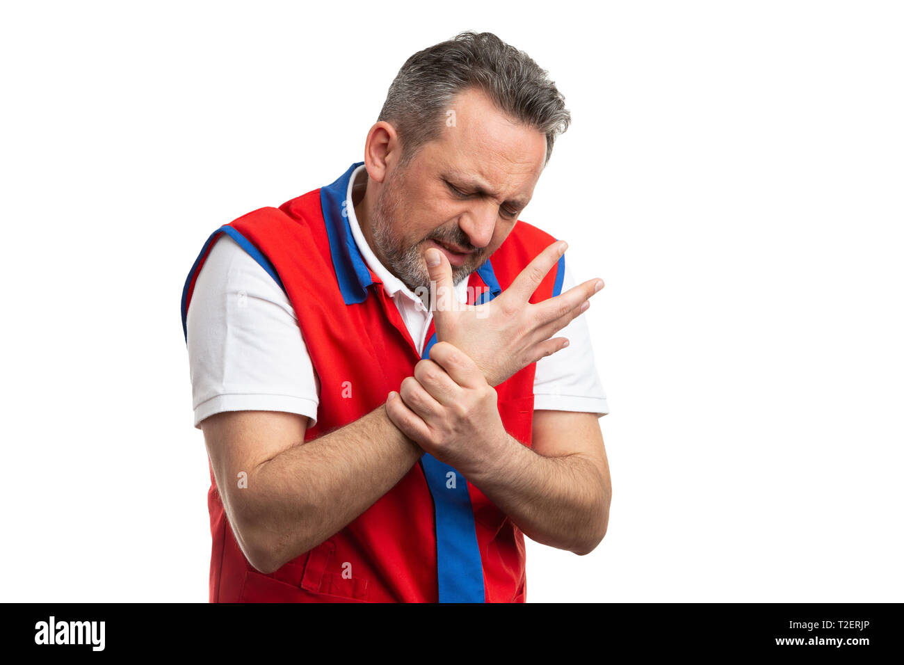 Male hypermarket or supermarket employee with painful expression holding sprained wrist as physical effort concept isolated on white - Stock Image