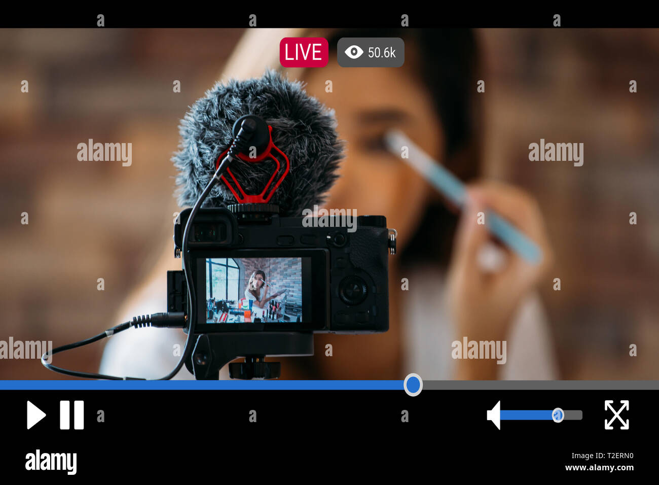 Young beautiful woman recording live stream video for makeup and cosmetics business purpose online with video player interface - Stock Image