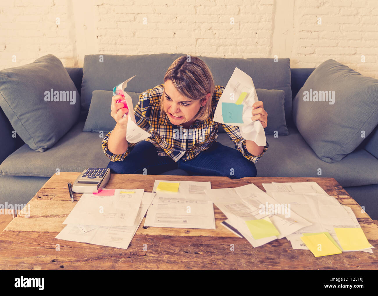 Portrait of furious and desperate young woman feeling stressed while working through finances. Sitting on the sofa making angry gestures. In paying de - Stock Image