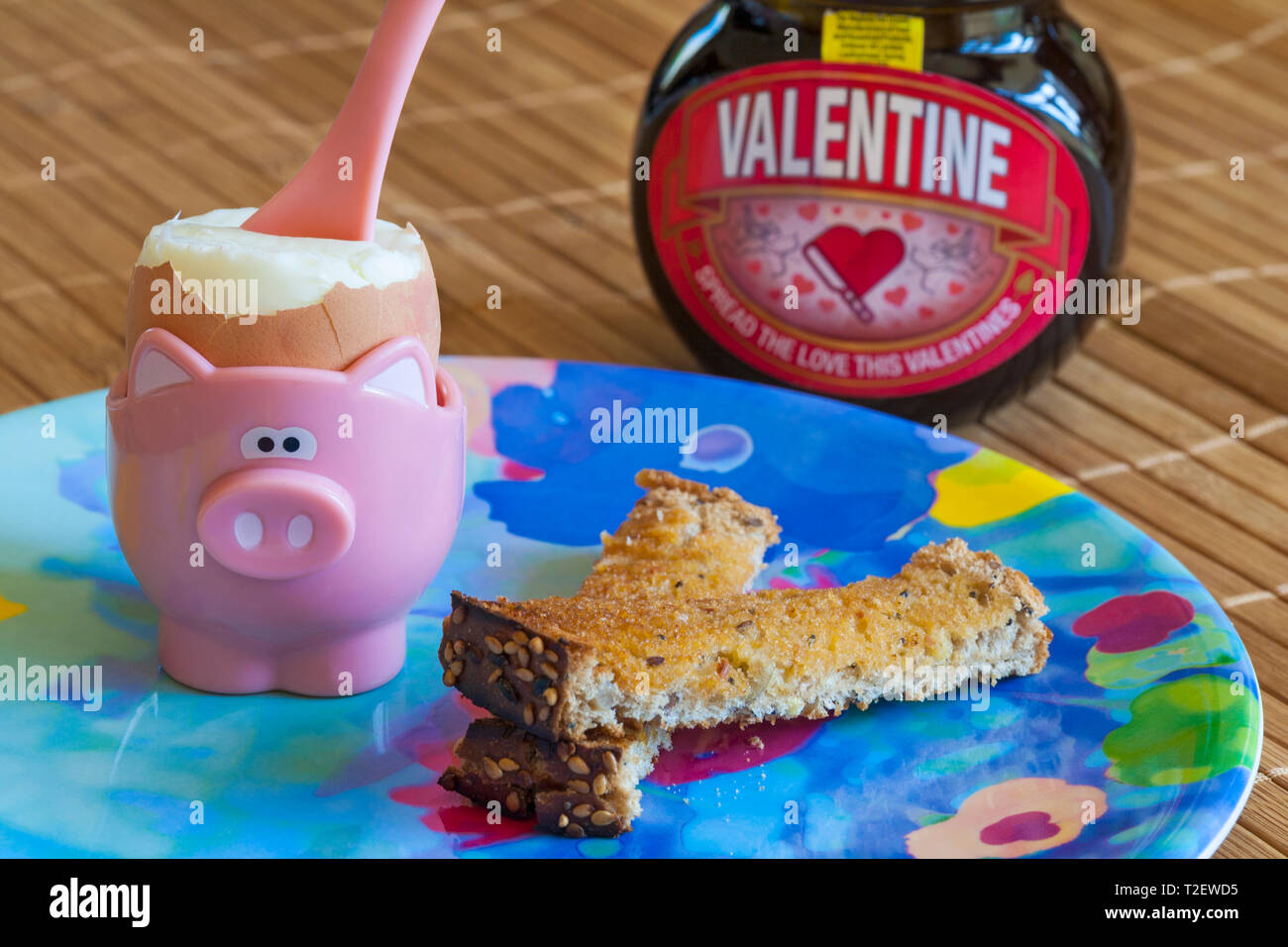 Boiled egg in egg cup with soldiers toast and jar Special edition jar of Valentine Marmite by Unilever - Stock Image