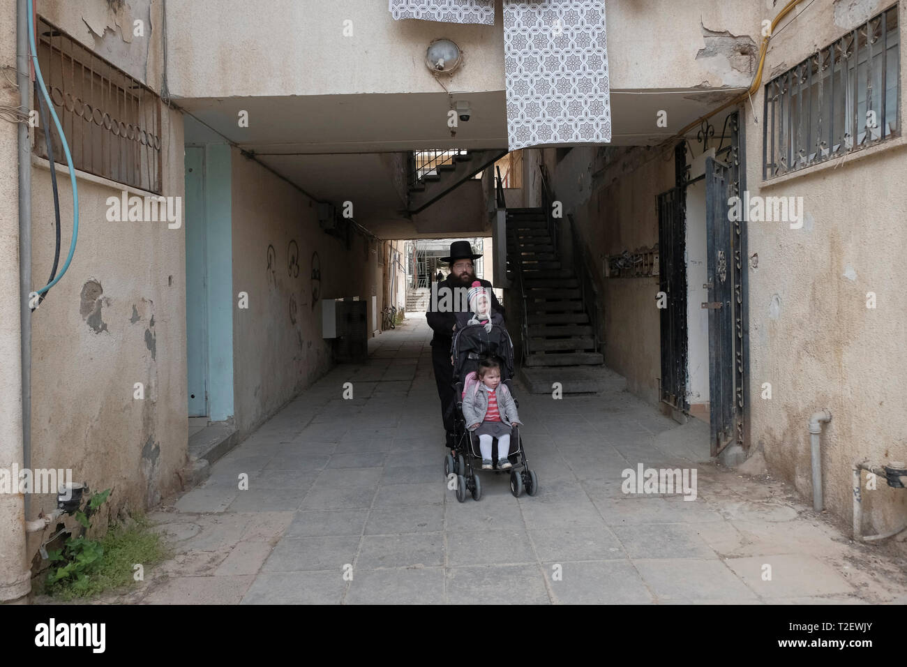 An ultra orthodox Jew walking in Shechunat Yeelim (the ibex neighborhood) in Arad a city in the Southern District of Israel. Gur hasidim and secular Jews in Arad have been at loggerheads for years. Secular residents accuse Gur hasidim of attempting to take over the city and harm their way of life, while the local Gur population contend that the city is refusing to provide them with basic municipal services. Stock Photo