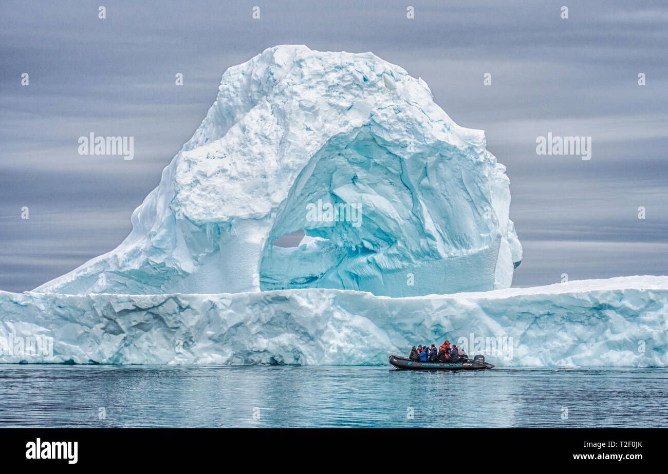Passengers on a zodiac cruise in Antarctica enjoying the view of a massive iceberg while on an expedition cruise to the Polar region - Stock Image