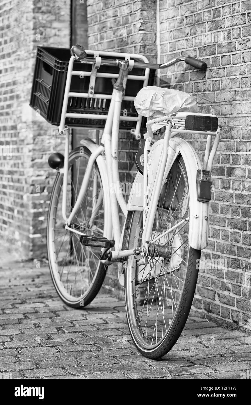 Retro style white bicycle parked against a brick wall, Amsterdam, The Netherlands - Stock Image