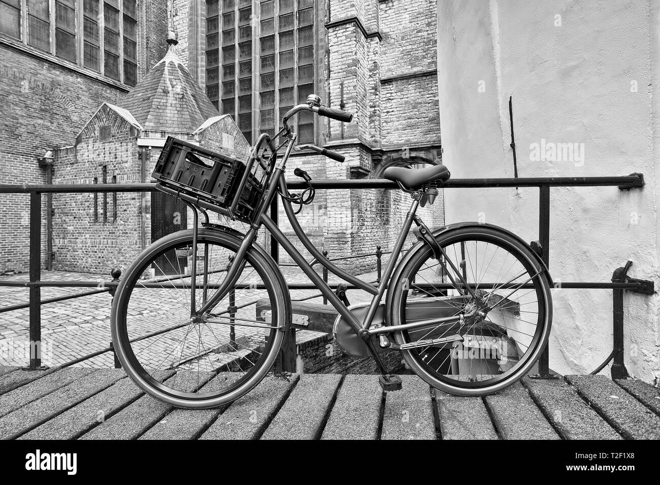 Retro style black bicycle parked against a railing, Gouda, The Netherlands - Stock Image