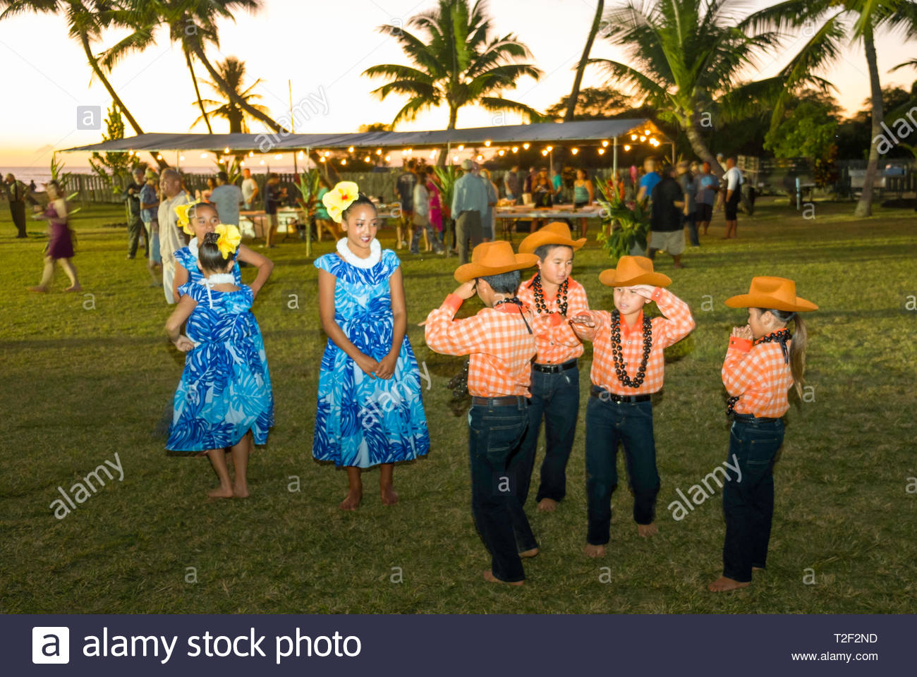 ae2f4277 Young children wearing Paniolo or Hawaiian cowboy costumes featuring orange  palaka shirts, jeans and cowboy