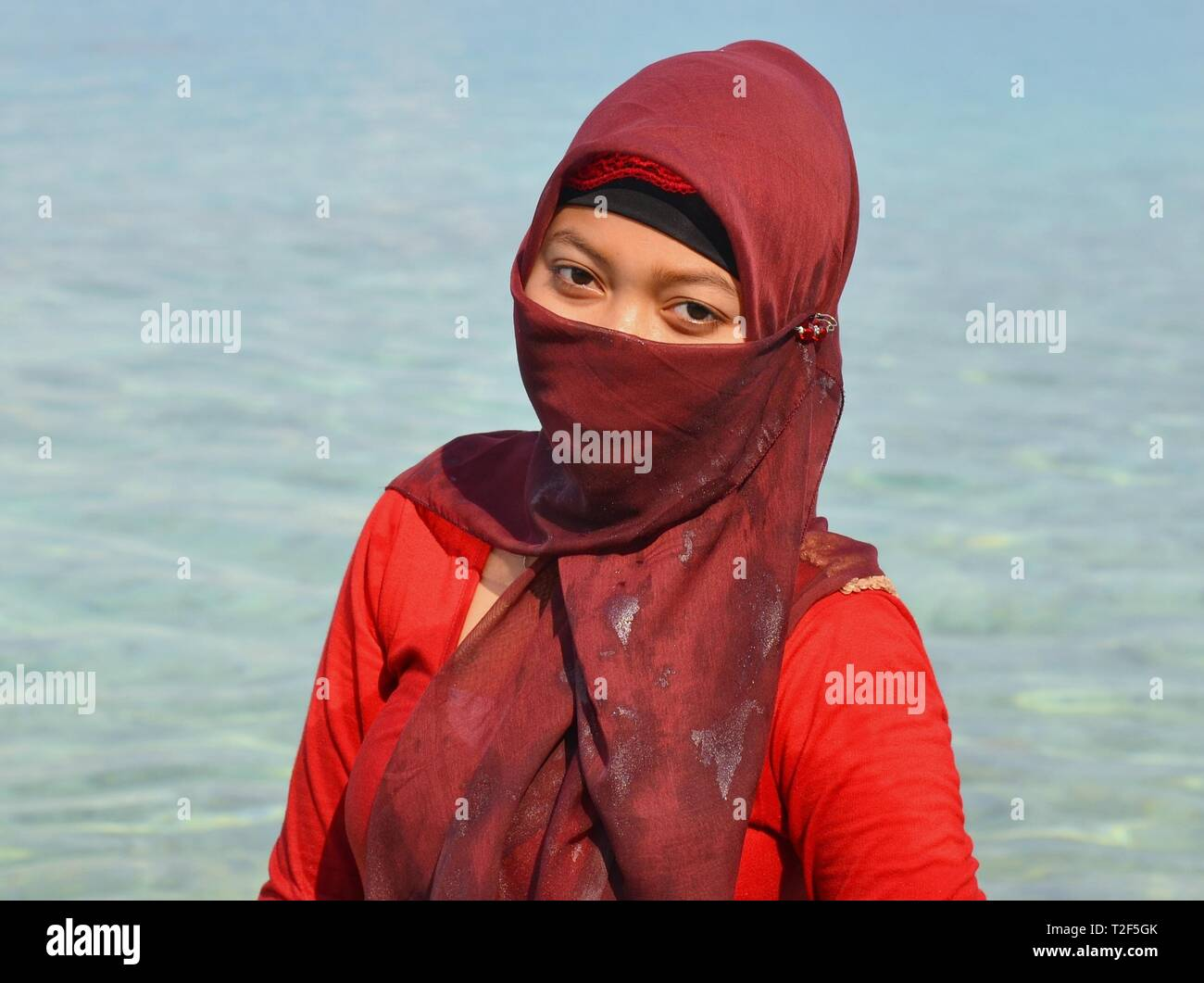 Indonesian Muslim girl at the beach wears a wet, maroon-coloured hijab with a face veil (yashmak) and poses for the camera. - Stock Image