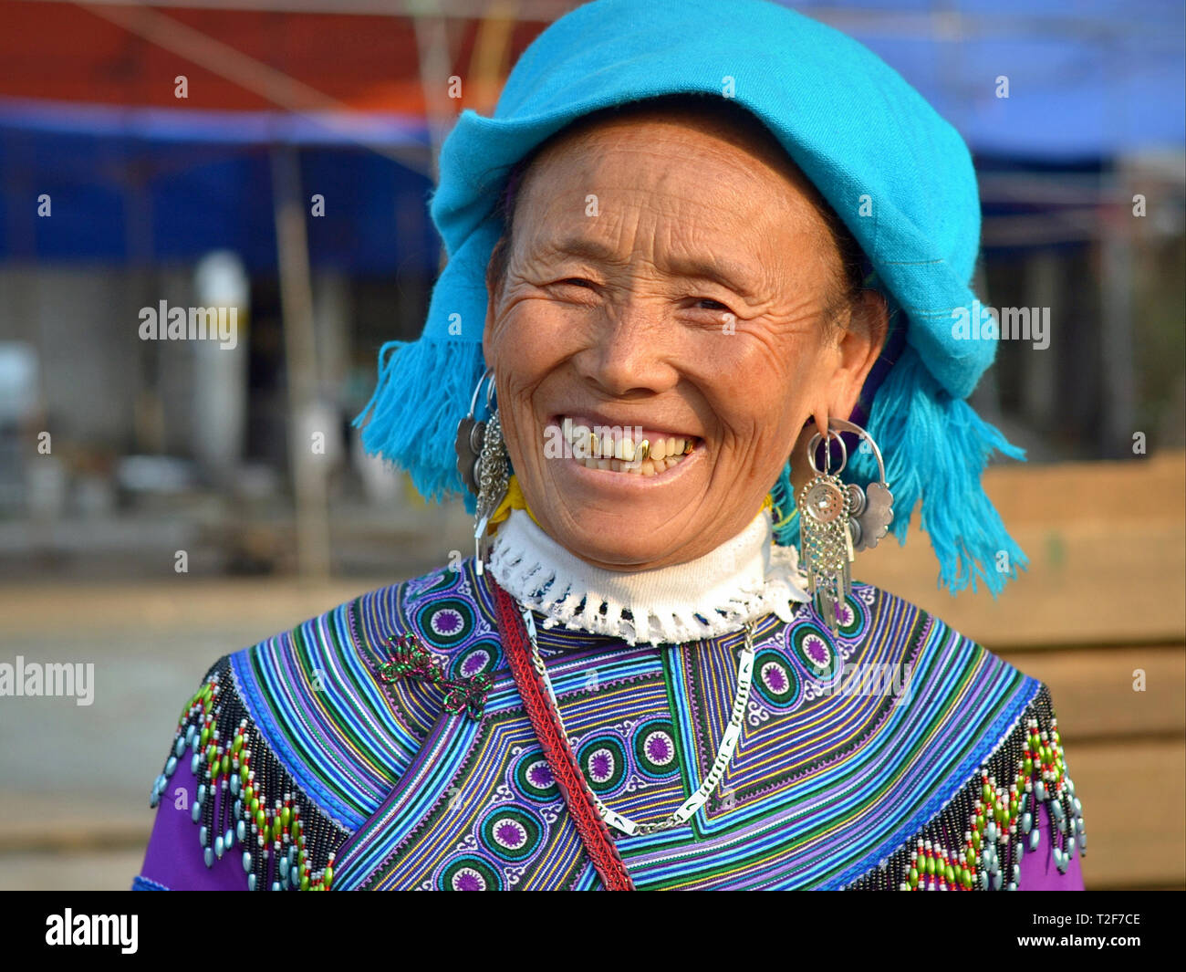 Elderly Vietnamese Blue H'mong hill-tribe woman with three gold teeth wears traditional H'mong embroidery in blue and smiles for the camera. - Stock Image