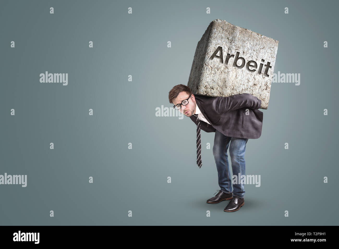 "Concept of an entrepreneur bending under a heavy workload. Translation on stone: ""Work"" - Stock Image"