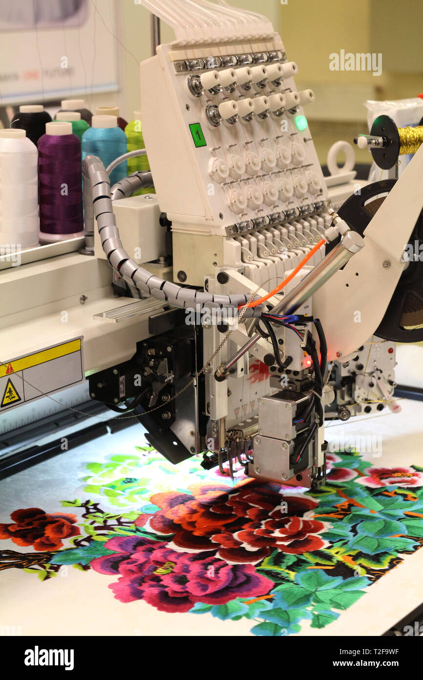 Textile manufacture. The machine embroiders a floral pattern. Factory for the production of clothing. - Stock Image