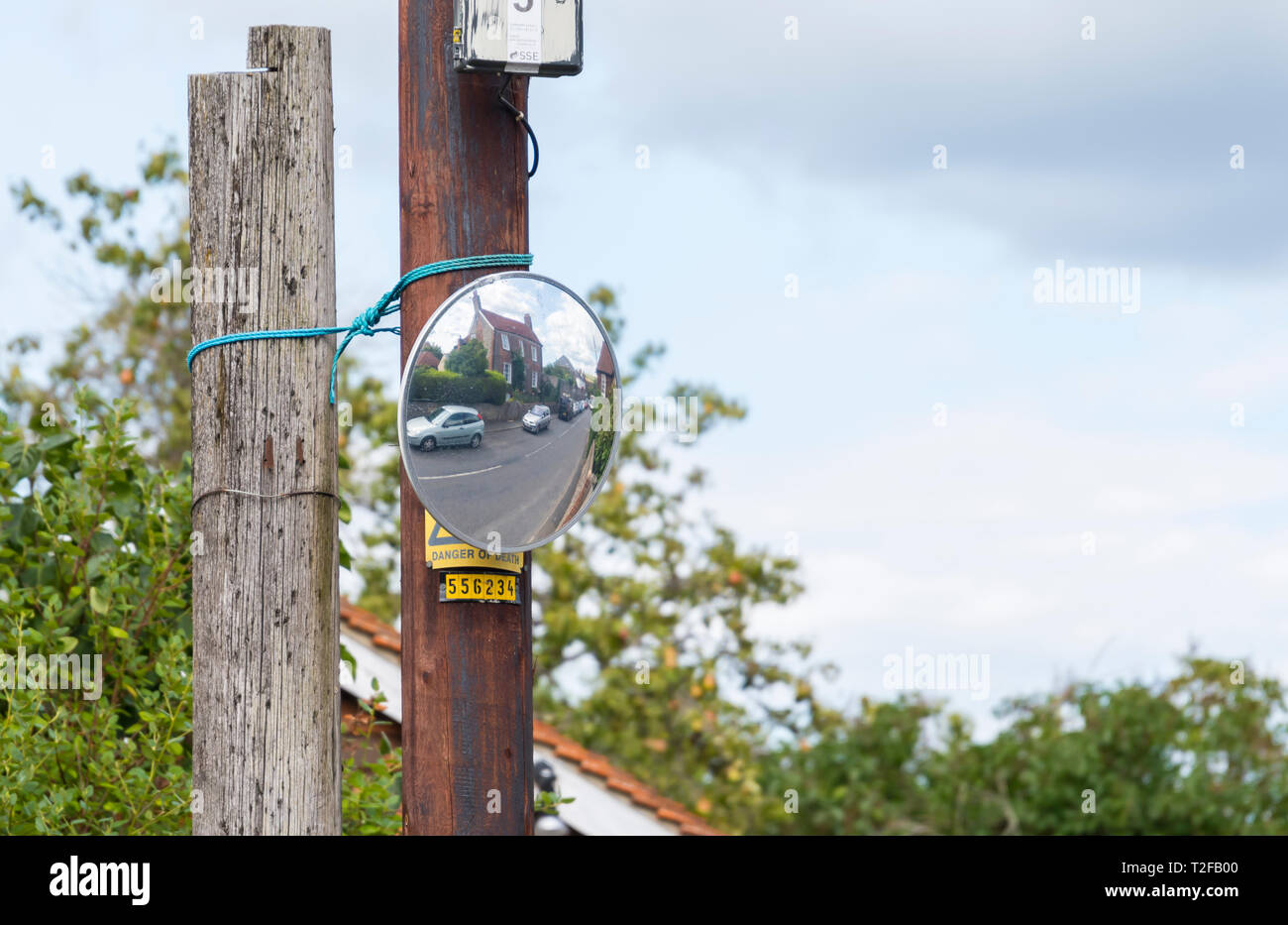 Convex mirror on a pole on a road in the UK to aid visibility at a blind junction. - Stock Image