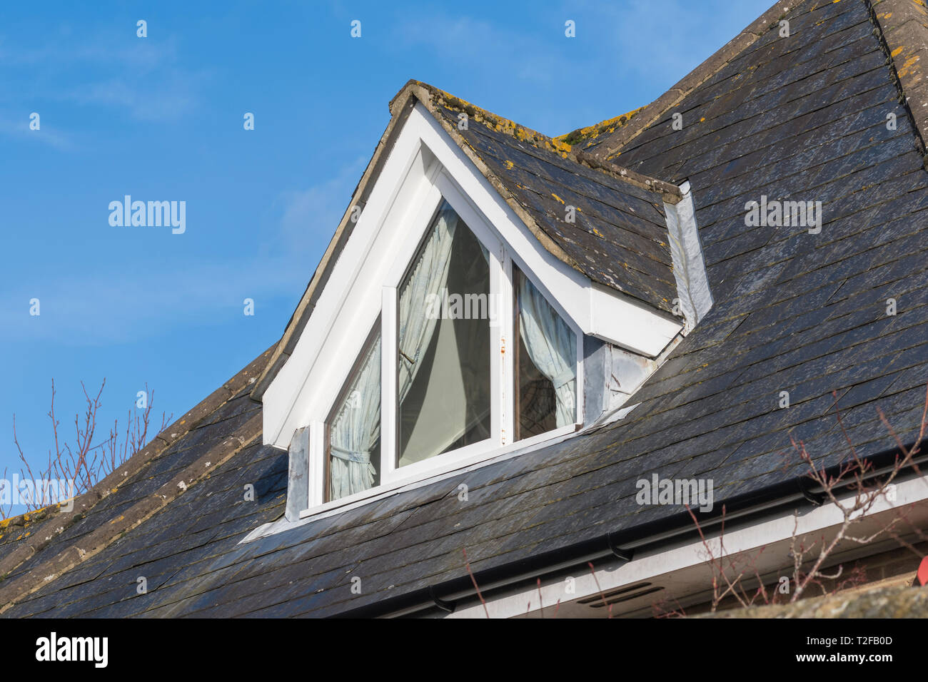 Dormer window protruding from a roof in the UK. Loft window. - Stock Image