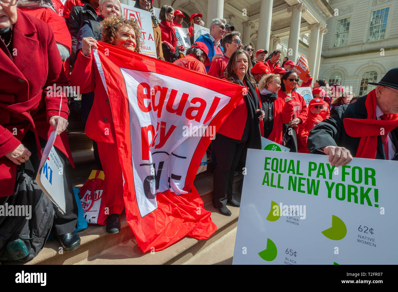 New York, USA. 02nd Apr, 2019. Activists, community leaders, union members and politicians gather on the steps of City Hall in New York on Tuesday, April 2, 2019 to rally against pay disparity on the 13th annual Equal Pay Day. Worldwide women on average earn 87 cents for every dollar her male counterpart earns with dramatic adjustments for women of color. Credit: Richard Levine/Alamy Live News - Stock Image
