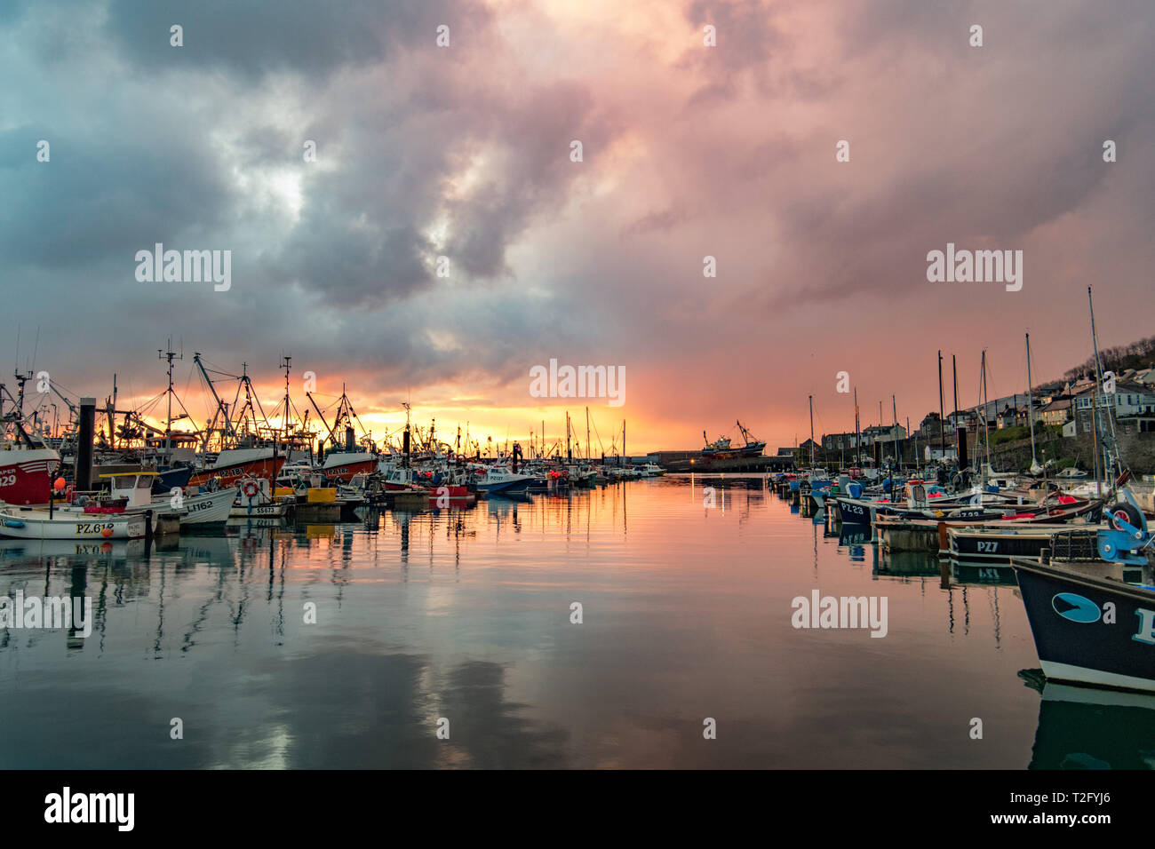 Newlyn, Cornwall, UK. 3rd Apr, 2019. UK Weather. A brief splash of colour at Newlyn Harbour this morning, before the sun dissapeared behind a thick band of clouds. Feeling much colder than yesterday. Credit: Simon Maycock/Alamy Live News Stock Photo