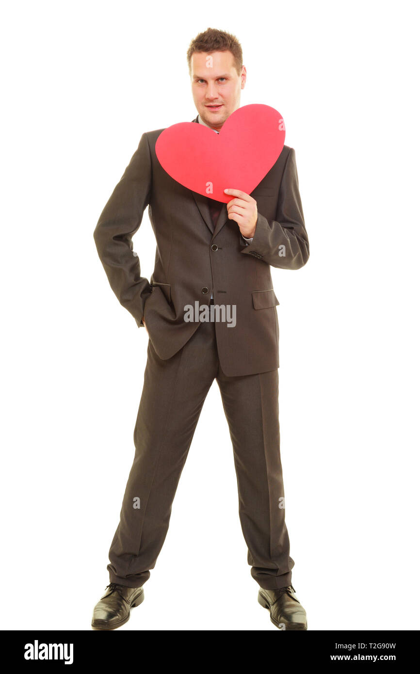Adult flirting guy in elegant suit holding heart made of paper, love symbol - Stock Image